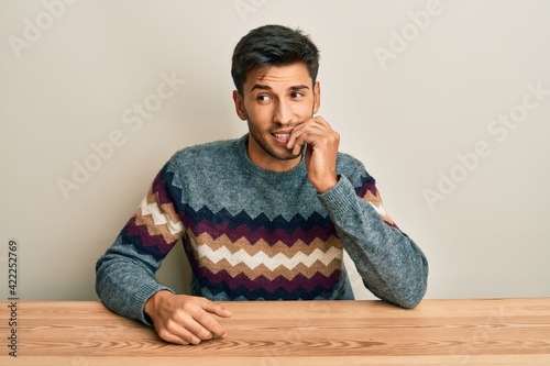 Photo Young handsome man wearing casual sweater sitting on the table looking stressed and nervous with hands on mouth biting nails