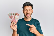 Young Handsome Man Holding 100 New Zealand Dollars Banknote Smiling Happy Pointing With Hand And Finger