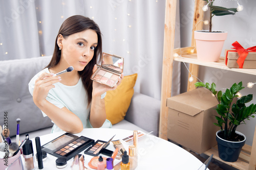 Woman beauty blogger shows tutorial on natural makeup and facial skin care at home