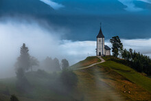 Jamnik, Slovenia - Foggy Summer Morning At Jamnik St.Primoz Hilltop Church. The Fog Gently Goes Around The Small Hilltop Chapel With Green Fields And Animals On The Top Of The Hill