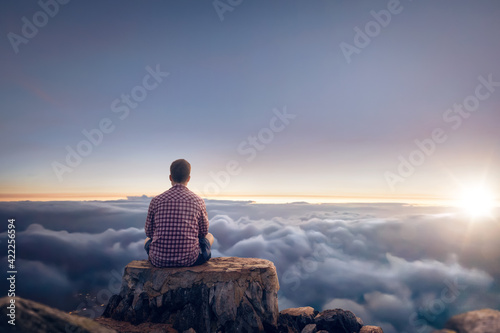 Man sitting on a summit above the clouds during sunrise