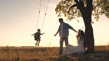Parents Swing A Happy Child High Up On A Swing At Sunset, A Cheerful Family In The Glare Of The Sun Plays With Their Daughter In A Pilot, Father Mother And Kid Baby Greet The Dawn On A Holiday Trip On