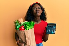 Beautiful African Young Woman Holding Groceries And Calculator Puffing Cheeks With Funny Face. Mouth Inflated With Air, Catching Air.