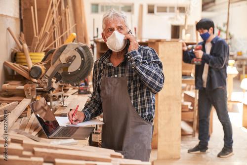 Billede på lærred Handwerker mit Maske mit Handy im Kundengespräch