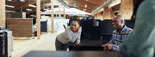 Canvas Group of young African American businesspeople laughing together during a casual meeting in a modern office