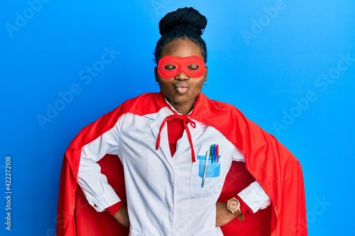 Slika na platnu Young african american woman wearing doctor uniform and super hero costume looking at the camera blowing a kiss being lovely and sexy