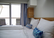 Modern Interior Design Balcony Or Verandah Cabin Stateroom With Double Queen Bed, Couch, Vanity Desk, Decoration Pillows And Duvet And Carpet With Stripes Onboard Luxury Cruiseship Or Cruise Ship Line