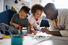 Father With Two Small Children Drawing Pictures At Home, Multi Ethnic Family And Home Schooling.