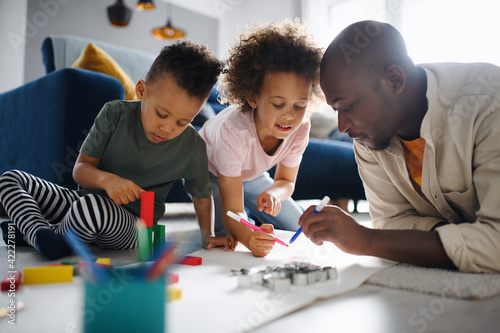 Father with two small children drawing pictures at home, multi ethnic family and home schooling Fototapeta