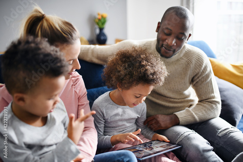 Multi ethnic family with two small children using tablet at home.