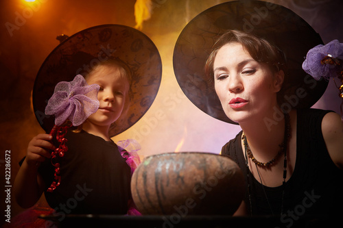 Fotografiet Beautiful brunette mother and cute little daughter looking as witches in special dresses and hats conjuring with a pot in room decorated for Halloween