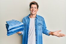 Handsome Caucasian Man Holding Stack Of Folded Jeans Celebrating Achievement With Happy Smile And Winner Expression With Raised Hand