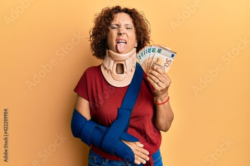 Beautiful middle age mature woman wearing cervical collar and sling holding insurance euros sticking tongue out happy with funny expression.