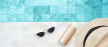 White Sunglasses, Sunscreen Bottle And Hat Near Swimming Pool In Luxury Hotel. Summer Travel, Vacation, Holiday And Weekend Concept