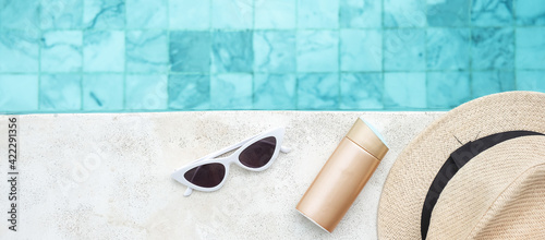 Photo white sunglasses, sunscreen bottle and hat near swimming pool in luxury hotel