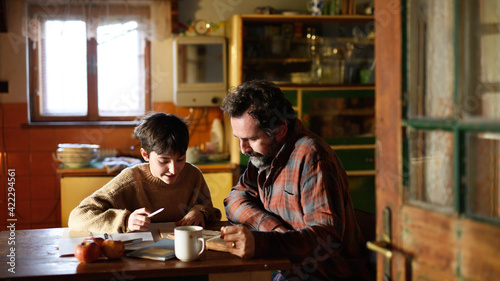 Obraz Poor mature father and small daughter learning indoors at home, poverty concept. - fototapety do salonu