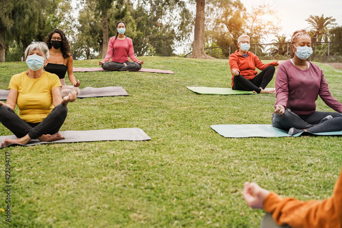 Fototapeta People doing yoga class outdoor sitting on grass while wearing safesty masks dur