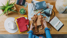 Top View Of Young Woman Packing For Vacation Trip Holiday, Desktop Travel Concept.