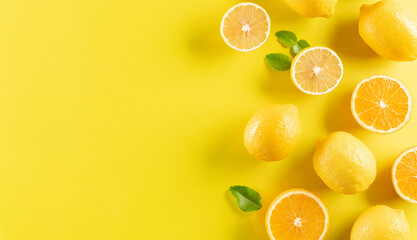 Summer composition made from oranges, lemon and green leaves on pastel yellow background. Fruit minimal concept.