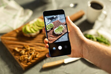 Hands Take Pictures On Smartphone Of Two Beautiful Healthy Sour Cream And Avocado Sandwiches Lying On Board On The Table. Social Media And Food Concept