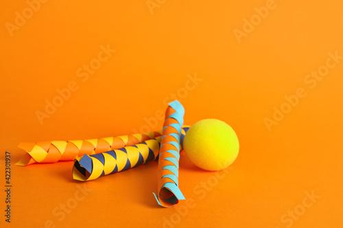 Slika na platnu Chinese finger traps and clown nose on orange background