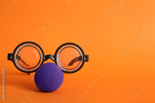 Fotografija Glasses and clown nose on orange background, space for text