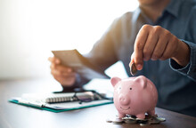 Close-up Image Of Man Hand Putting Coins In Pink Piggy Bank For Account Save Money. Planning Step Up, Saving Money For Future Plan, Retirement Fund. Business Investment-finance Accounting Concept.