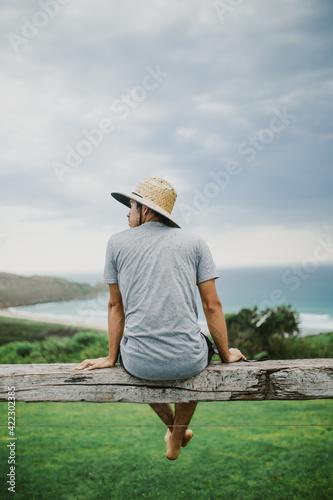 Obraz fotografía vertical de un hombre joven con sombrero sentado sobre una viga de madera de un mirador con una playa de fondo, mirando hacia el costado izquierdo - fototapety do salonu