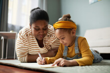 Portrait Of Cute African-American Girl Drawing On Floor With Mother In Cozy Home Interior