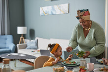 Portrait Of African-American Family Enjoying Dinner Together In Minimal Home Interior, Focus On Grandmother Serving Food To Cute Little Girl, Copy Space