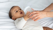 Cute Little African American Infant Drinking From Baby Bottle