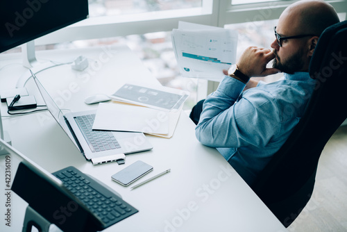 Thoughtful businessman examining reports during work in light office
