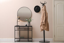 Console Table, Clothes Rack And Mirror On Beige Wall In Hallway. Interior Design