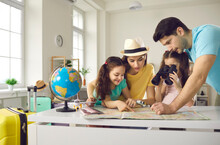Family Vacation Planning, Worldwide Travelling, Booking Flight Ticket. Happy Mother And Father With Daughter Children Searching Tourist Route On Paper Map, Choosing Country To Travel, Tropical Resort