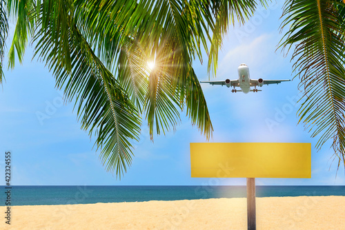 Blank yellow sign and commercial plane flying on blue sky with coconut palm leaves and tropical beach background. Copy space concept and happiness travel idea