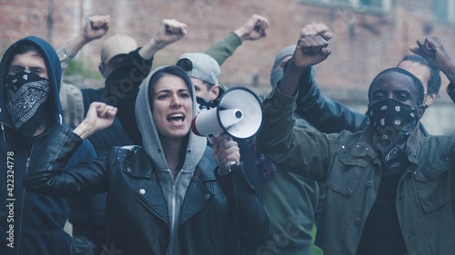 Obraz na plátně Pretty young Caucasian girl screaming in megaphone while standing among people at protest against racism and police brutality