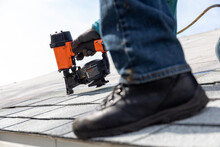 Roofer Installing Roof Shingles With Nail Gun
