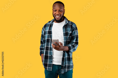Cheerful Black Man Using Smartphone Texting Standing Over Yellow Background