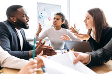 Angry Business Partners Sitting In Office On Negotiations, Cant Coming To Agreement. Multiethnic Colleagues Arguing, Blame Each Other, Failed A Startup, Unsuccess Concept