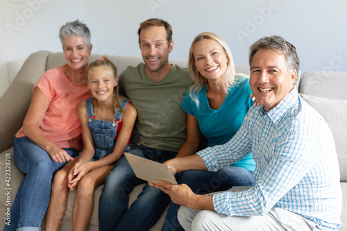 Smiling caucasian grandparents on couch with granddaughter and her parents looking at tablet