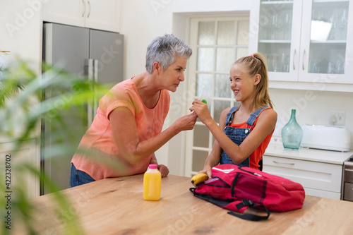 Senior grandmother giving granddaughter packed lunch and lollipop in kitchen