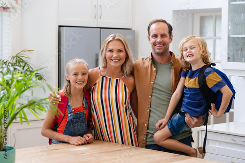 Portrait of smiling caucasian parents with son and daughter wearing school bags embracing in kitchen