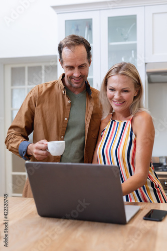 Smiling caucasian couple looking at laptop together and drinking coffee in kitchen