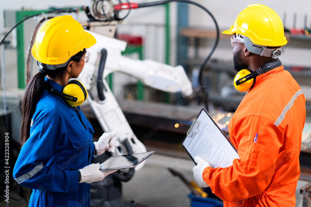 Fototapeta engineer cooperation male and female technician maintenance control relay robot arm system welding with tablet laptop to control quality operate process work heavy industry 4.0 manufacturing factory