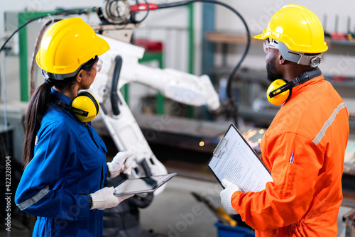Obraz engineer cooperation male and female technician maintenance control relay robot arm system welding with tablet laptop to control quality operate process work heavy industry 4.0 manufacturing factory - fototapety do salonu