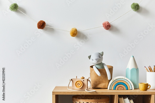 Obraz Stylish scandinavian newborn baby room with toys, plush animal, photo camera and child accessories. Cozy decoration and hanging cotton balls on the white wall. Copy space. - fototapety do salonu