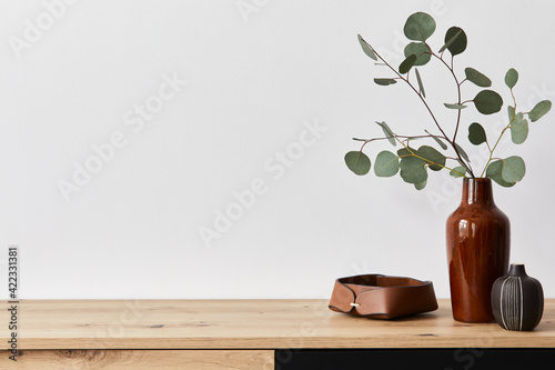 Fototapeta Minimalist concept of living room interior at elegant apartment with wooden commode, leaf in ceramic vase and elegant personal accessories in modern home decor. Copy space. Template. . obraz