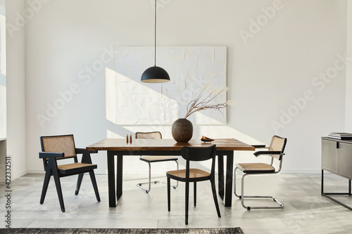 Fototapeta Minimalist composition of dining room interior with wooden table, design chairs, dried flowers in a vase, black pendant lamp, art paintings on the wall and elegant personal accessories. Template. obraz