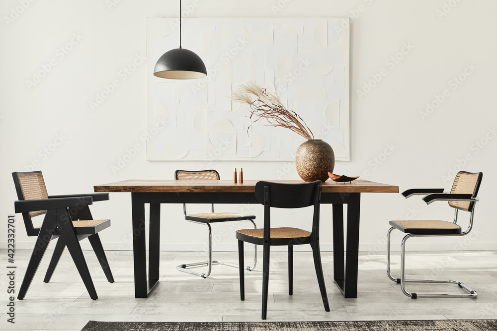 Fototapeta Minimalist composition of dining room interior with wooden table, design chairs, dried flowers in a vase, black pendant lamp, art paintings on the wall and elegant personal accessories. Template.