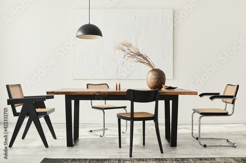 Obraz Minimalist composition of dining room interior with wooden table, design chairs, dried flowers in a vase, black pendant lamp, art paintings on the wall and elegant personal accessories. Template. - fototapety do salonu